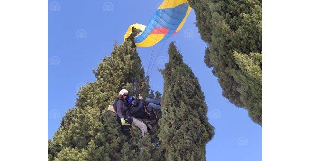 Yamaç paraşütü pilotu ile yolcusunu ağaç dalları kurtardı